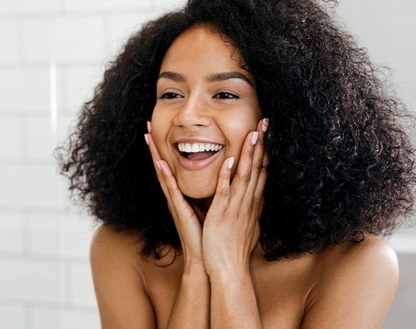 mujer sonriendo por el uso de Máscara de carbón activado