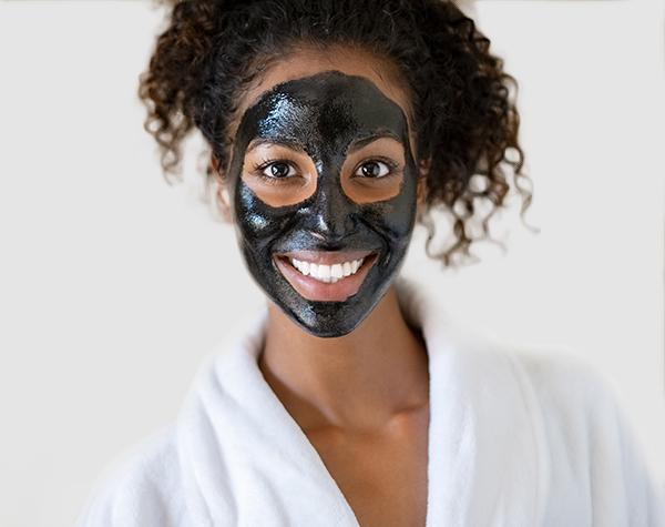 mujer morena con mascara de carbon activado